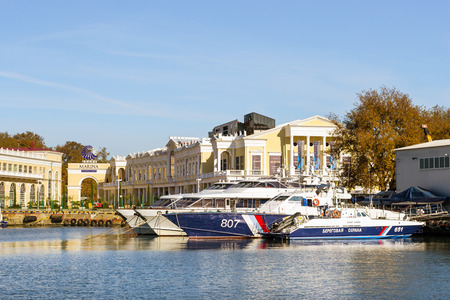 complex navigation: Sochi, Russia - November 1, 2015: Rescue and border guard motorboat moored at pier in Sochi seaport. In background the shopping gallery Grand Marina. Marine station complex Port. Krasnodarskiy kray, Russia Editorial