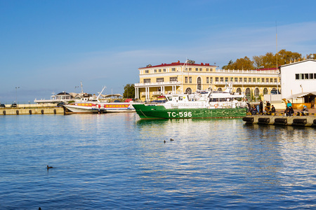 complex navigation: Sochi, Russia - November 1, 2015: Rescue and border guard motorboat moored at pier in Sochi seaport. Fishermen catch fish with fishing rods. Marine station complex Port. Krasnodarskiy kray, Russia Editorial