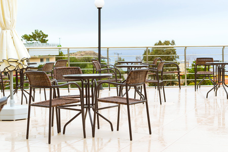 Round tables with wicker chairs outside on veranda of restaurant, overlooking the Cretan sea. Resort hotel, Bali, Rethymno, Crete, Greece