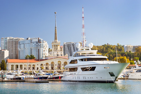 complex navigation: Sochi sea port view from water. Luxury yachts and private boats moored at pier. In background architecture modern resort town, hotels and sanatoriums. Marine station complex Port. Krasnodarskiy Russia