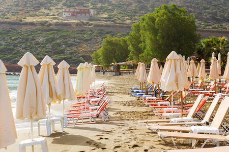 Sunny sandy Livadi beach in sea bay of resort village Bali. Views of mountain, shore, washed by waves and sun loungers with parasols where sunbathing tourists. Bali, Rethymno, Crete, Greece