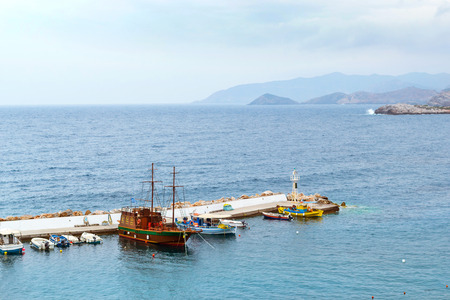 Harbour with marine vessels, boats and lighthouse. View from cliff on Bay with marine braid. Bali - vacation destination resort, with secluded beaches and clear ocean waters. Rethymno, Crete, Greece