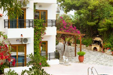 residential tree service: Modern and classic resort Greek architecture, new white building in constructivist style, stands on shore of Cretan sea. Resort village Bali, Rethymno, Crete, Greece