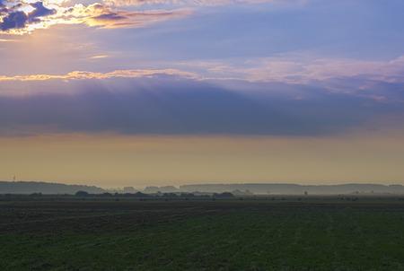 amanecer: Amanecer brumoso en la mañana del comienzo del verano en el pueblo. se arrastra aire fresco y de la niebla de la mañana sobre campo de siembra y pasto. paisaje rural en tonos cálidos, sin gente. Los rayos del sol que se rompe a través de las nubes
