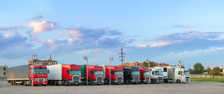 Heavy trucks with trailers loaded with merchandise, stand in a row on an asphalt car platform. International cargo transportation and logistics. Road transport infrastructure, industrial landscape Stock Photo