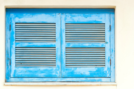 rethymno: Blue wooden window shutters with vents in white stone wall. Classic resort Greek architecture, white-blue building of house on shore of Cretan sea. Resort village Bali, Rethymno