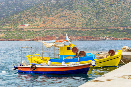 Fishing harbor with marine vessels, boats and lighthouse. Sea view at bay. Bali is vacation destination resort, with secluded beaches. Rethymno, Crete, Greece