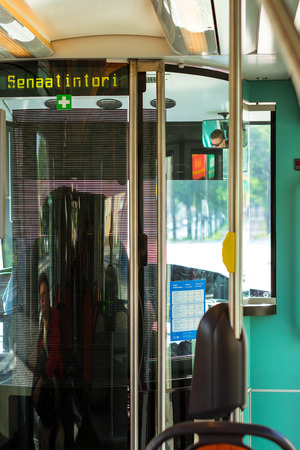 Helsinki, Finland - August 5, 2012: Modern green tram. Stylish interior of tram with comfortable seating, railings and transponders. City public high-tech electric vehicle in industrial metropolis