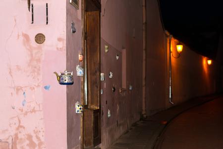 Vilnius, Litauen - 7. August 2012: Keramische Teekannen der Weinlese eingebettet in der Fassadenecke des historischen Gebäudes auf Hauptstraße der alten Stadt. Die Aufschrift auf dem Wasserkocher zeigt die Adresse der Bernardine-Straße an Standard-Bild - 74503683