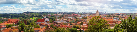 Panorama of Vilnius from top of mountain of Gediminas Tower. View of red rooftops of old town, spires and towers of cathedrals & churches. River Vilia parts of historic & business districts. Lithuania