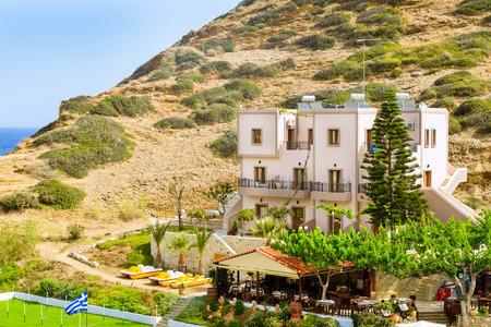 Comfortable hotel and tavern buildings. Resort Greek architecture. Sandy Evita and Karavostasi beach in sea bay of resort village Bali. Rethymno, Crete, Greece