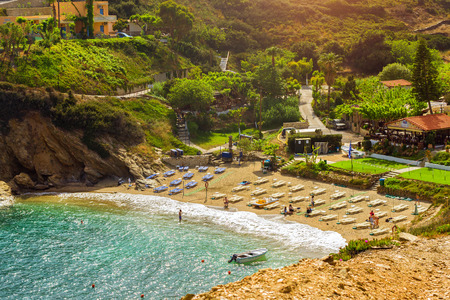 Bali, Greece - April 30, 2016: Sandy Evita and Karavostasi beach in sea bay of resort village Bali. Views of shore, washed by waves and sun loungers with parasols where sunbathing tourists