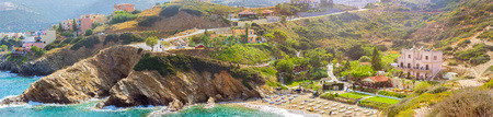 Sandy Evita and Karavostasi beach in sea bay of resort village Bali. Views of shore, washed by waves and sun loungers with parasols where sunbathing tourists. Hotel and tavern buildings. Crete, Greece