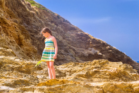Sweet girl stands on top of a cliff on background of blue sky in stormy windy weather. Active rest on the rocky shore of the beach in resort village Bali, Crete island, Greece, Beach Evita