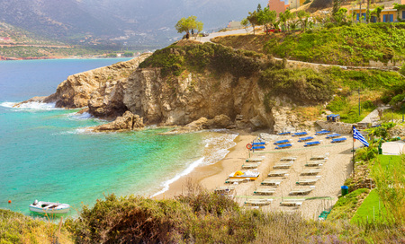 Sandy Evita and Karavostasi beach in sea bay of resort village Bali. Views of shore, washed by waves and sun loungers with parasols where sunbathing tourists. Bali, Rethymno, Crete, Greece
