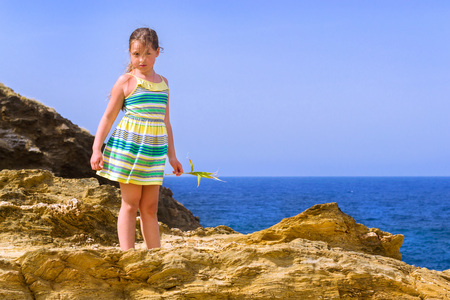 Sweet girl stands on top of a cliff on background of blue sky and sea in stormy windy weather. Active rest on the rocky shore of the beach in resort village Bali, Crete island, Greece, Beach Evita