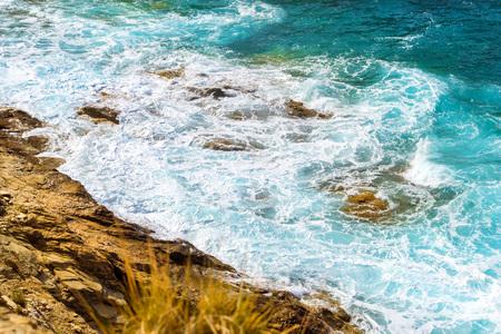 Waves break on rocky shore. Raging sea an elemental power in a storm. Clear day at sea coast. Tourist beach resort in village Bali, Crete island, Greece, Beach Evita