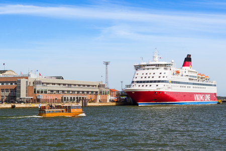 suomi: Helsinki, Finland - August 4, 2012: Cargo-passenger cruise ferry Viking Line moored in Bay at pier in Helsinki port. Passengers boarding from terminal. Wooden boat with tourists navigate in South Gulf Editorial