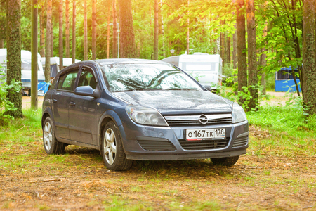 HAMINA, FINLAND - JUNE 13, 2014: Summer outdoor recreation, Scandinavian vacation. Car Opel Astra H parked in a wooded campsite among pine trees. Finnish Gulf. Area for camp in woods. Hamina, Finland, Suomi