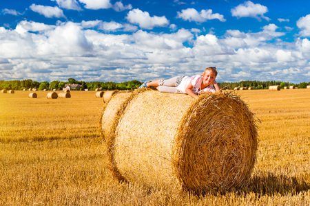 Cute young girl having fun on haystack. Stacks of straw - bales of hay, rolled into stacks left after harvesting of wheat ears, agricultural farm field with gathered crops rural. Pargi, Voka, Estonia Stock Photo