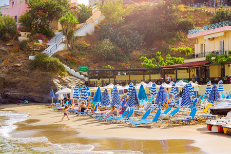 Bali, Greece - April 30, 2016: Sandy Evita and Karavostasi beach in sea bay of resort village Bali. Views of shore, washed by waves and sun loungers with parasols where sunbathing tourists. Crete