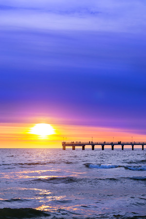 Pedestrian pier extends into the sea. Sunset at Baltic sea in resort Palanga, Lithuania. Rays of sun shine through the low cirrus clouds. Tidal waves wash the sandy beach in cloudy weather Stock Photo