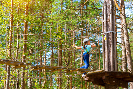 Teenage girl goes on hinged trail in extreme rope Park in summer forest. High-altitude climbing training of child on adventure track, equipped with safety straps and protective helmet. Estonian summer