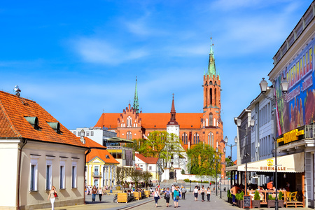 pavers: Bialystok, Poland - April 29, 2012: Tourists walk in sunny summer day on pavers central square of Kosciusko Market. On background Cathedral Basilica of Assumption of Blessed Virgin Mary in Bialystok