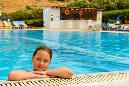 Cute little teenage girl in swimsuit playing and swimming in pool in middle of day. Relax and sunbathe by pool with clear blue water in Resort hotel, Atali Village. Bali, Rethymno, Crete, Greece Imagens