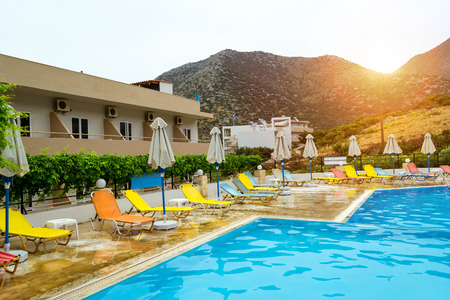 Bali, Greece - May 2, 2016: Relax and sunbathe by pool with clear blue water in Resort hotel Atali Village, 4 star. Empty pool without tourists early morning at hotel. Bali, Rethymno, Crete, Greece Editorial