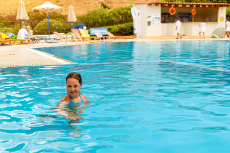 noon: Cute little teenage girl in swimsuit playing and swimming in pool in middle of day. Relax and sunbathe by pool with clear blue water in Resort hotel, Atali Village. Bali, Rethymno, Crete, Greece Stock Photo