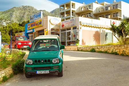 noon: Bali, Greece - may 2, 2016: Rental all-wheel drive car Suzuki are parked on sloping street leading to the sea, about office leasing transport. Resort village Bali, Rethymno, Crete, Greece Editorial