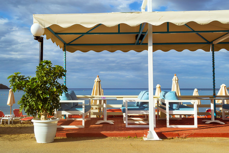 seafronts: Tables with thatched umbrellas are on the road at beach cafe on the seafront. Livadi beach in sea bay of resort village Bali in may. Bali, Crete, Greece Stock Photo