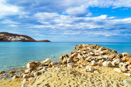 Breakwater of huge rocks going out to sea. Marine spit on beach Livadi in sea bay of resort village Bali in may. Views of mountain, shore, washed by waves where sunbathing tourists. Crete, Greece