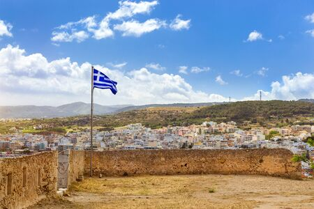 fortezza: Greek flag flies on flagpole on tower of castle Fortezza - Venetian fortress on hill Paleokastro in resort Rethymno. Greek architecture on coast of Kolpos Almirou. Crete island, Greece