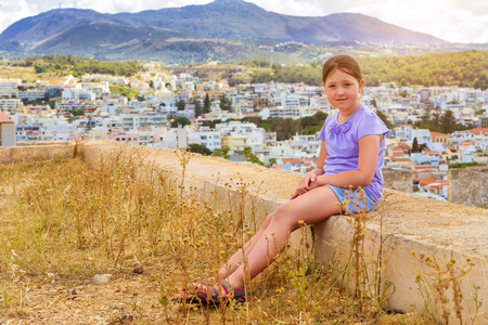 fortezza: Beautiful teenage girl sitting on background of resort Greek architecture Rethymno city-port, built by Venetians, from height of Fortezza Castle - fortress on hill Paleokastro. Crete, Greece