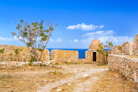 Inner courtyard & fortifications, surrounded by stone walls, Fortezza Castle - Venetian fortress with Bastion defense system on hill Paleokastro in resort Rethymno. Historical attractions Crete Greece Stock Photo