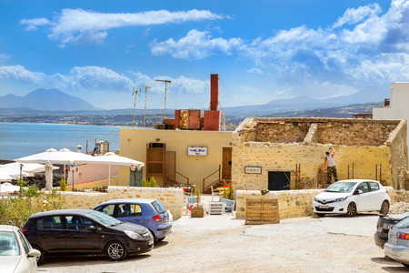 fortezza: Rethymno, Greece - May 3, 2016: Builder and stonemason restoring stone wall in classic resort architecture. Cozy resort buildings on Greek island Crete on sunny summer day