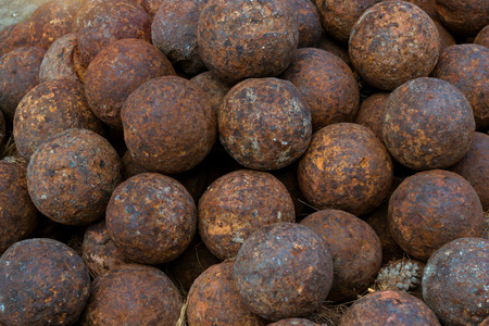 Texture of old cannonballs in courtyard of Fortezza Castle - Venetian fortress with Bastion defense system on hill Paleokastro in resort Rethymno. Greek historical attractions. Crete, Greece Stock Photo