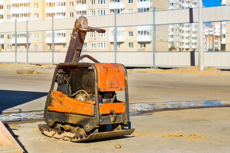 machinery: Manual ramming machine for compacting soil on construction of high-speed road around Krasnoe Selo, Saint Petersburg. Light mechanized tools and equipment for works at industrial construction. Russia Stock Photo