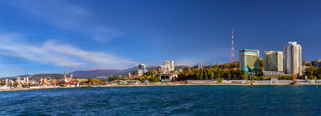 complex navigation: View from water at architecture of modern resort town Sochi, hotels, sanatoriums, television tower and Sochi sea port with luxury yachts moored at pier. Krasnodarskiy kray, Russia Stock Photo