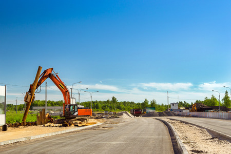 Crawler Excavator to hammer a steel piles into ground. Construction of high-speed bypass road around Krasnoe Selo, Saint Petersburg. Heavy machine equipment for excavation works in industry. Russia Stock Photo