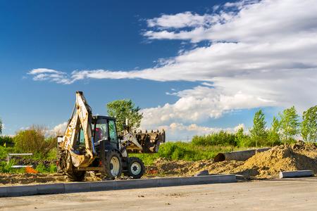 Tractor with bucket performs excavation work. Construction of high-speed bypass road around Krasnoe Selo, Saint Petersburg. Heavy machine equipment for excavation works industrial construction. Russia