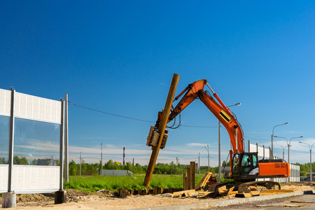sand quarry: Crawler Excavator to hammer a steel piles into ground. Construction of high-speed bypass road around Krasnoe Selo, Saint Petersburg. Heavy machine equipment for excavation works in industry. Russia Stock Photo