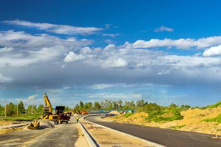 Rupsgraafmachine laadt vrachtwagen met puin met behulp van emmer. Bouw van high-speed bypass weg rond Krasnoe Selo, Sint Petersburg. Zware industriële machines apparatuur voor uitgraving. Rusland