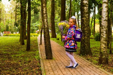 A little girl in her elementary school uniform with flowers posing in autumn landscape with her shoulder bag for her textbooks on her first day of school in September in Russia.