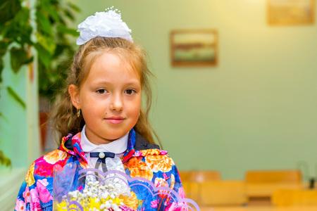 žák: Malý první grader, studentka ve škole v den znalostí - 1. září. Student základní školy v uniformě s luky představující ve třídě. Vzdělávání v Rusku Reklamní fotografie