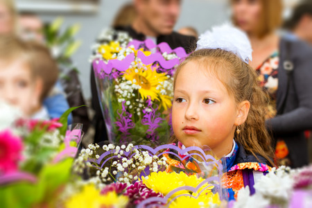 Little first-grader, girl-student goes to school on knowledge day - September First. Student of elementary school in uniform with bows and flowers. Russia Stock Photo