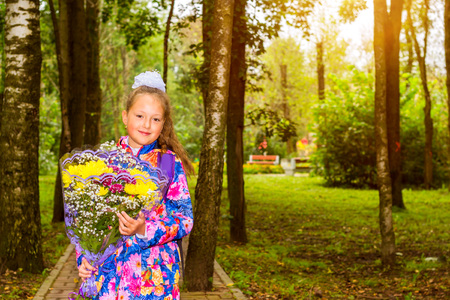 Little first-grader, girl-student goes to school on knowledge day 1. September. Student of elementary school in uniform with flowers posing in autumn landscape. Girl with shoulders bag. Russia