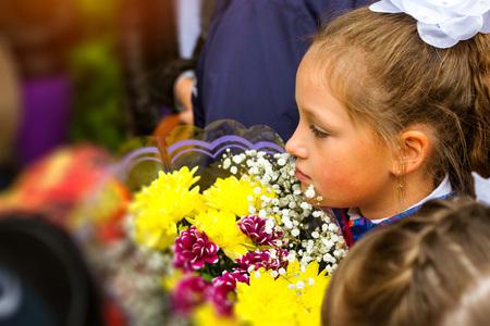 Malý prvotřídní student, studentka, chodí do školy v den znalostí - první září. Student základní školy v uniformě s luky a květinami. Rusko Reklamní fotografie